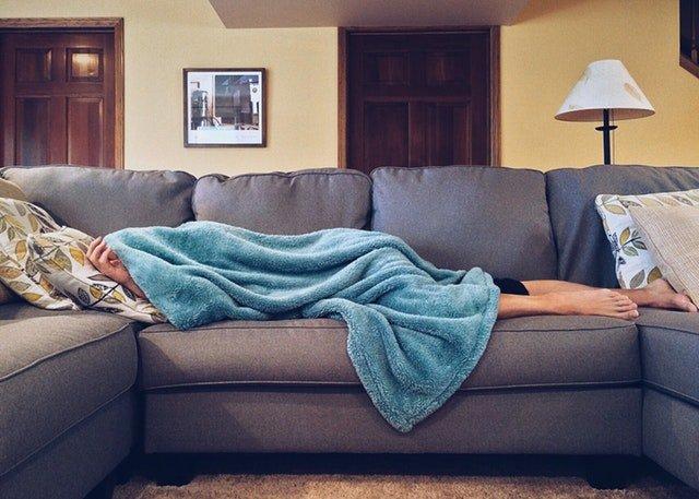 Muž spí na gauči zakrytý s dekou.jpg