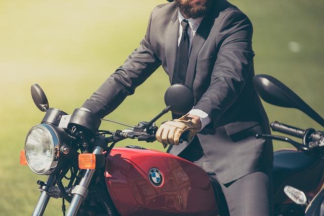 Muž v obleku sedí na motorke