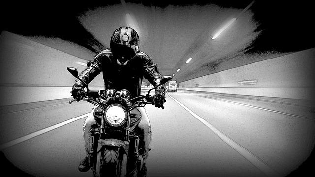 Kreslený čiernobiely obrázok muža s prilbou na hlave, idúceho na motorke v tuneli