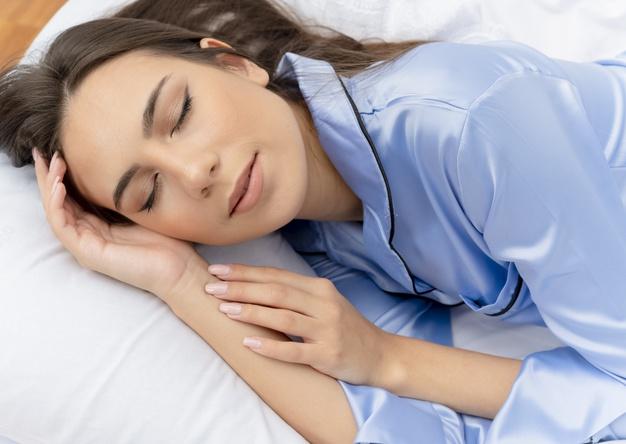 young-beautiful-woman-blue-pajamas-laying-bed_141793-47469